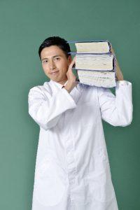 白衣を着て本を持つ男性